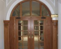 Heritage fire door with multiple vision panels and arched overlight.