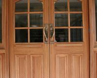 Heritage fire door set with raised bollection panels and multiple vision panels.